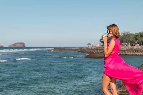photo human woman wearing pink dress standing on sea rock while holding cup photo free for commercial use images