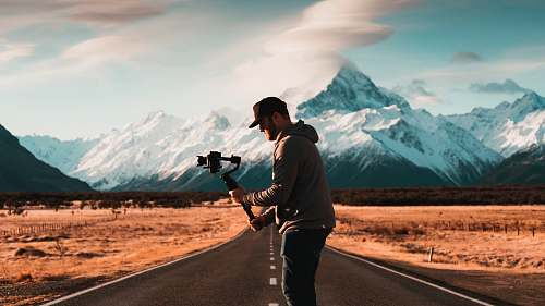 photo human man arranges his gimbal between empty narrow road person free for commercial use images