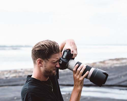 human man holding black bridge camera near sea person