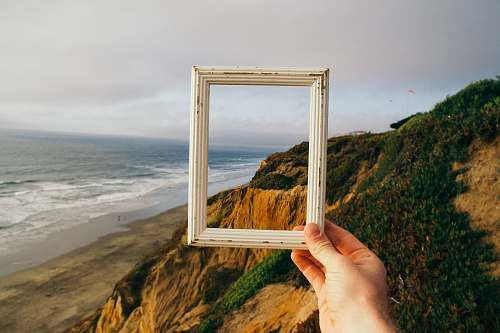 frame person hand holding photo frame ocean