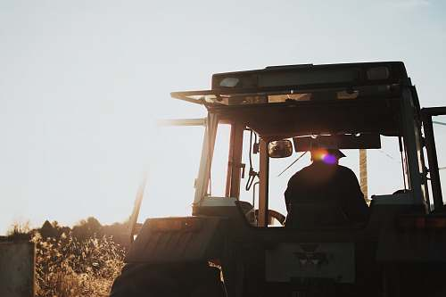 farming silhouette of man riding tractor agriculture