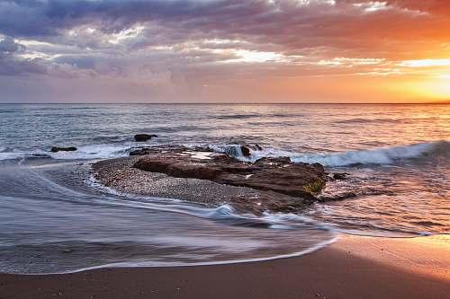 ocean brown stone near seashore during sunset coast