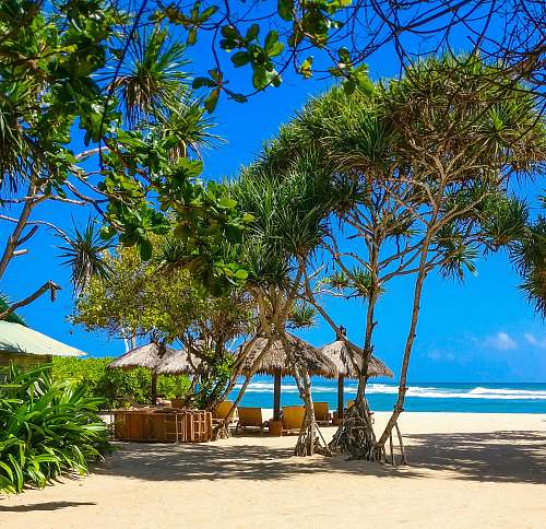sea four huts at beach under blue skies during daytime indonesia
