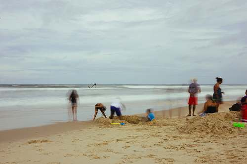 ocean group of people standing on beach shore sea