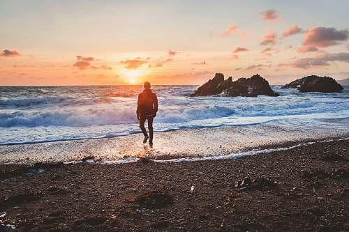 water man walking in beach during golden hour sea