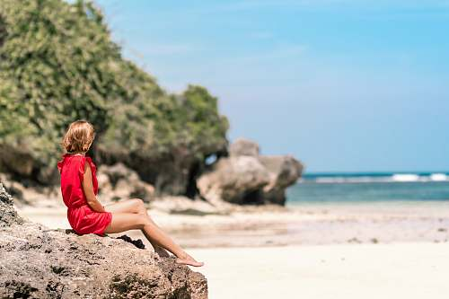 human selective focus photo of woman sitting on rock formation seashore person