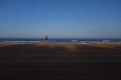 ocean woman in black one-piece swimsuit facing blue wavy ocean under clear blue sky sea