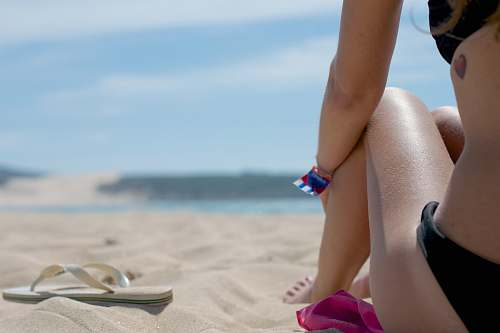 people woman sitting on sand beside flip-flop person