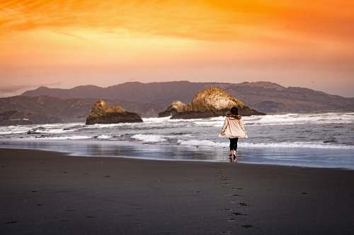 ocean woman wearing on seashore during sunset sea