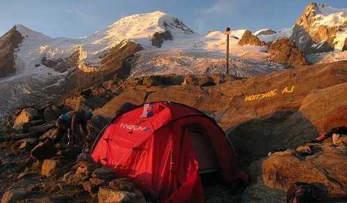 human red and black dome tent on mountain peak person