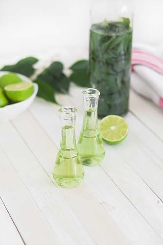 drink two clear glass bottles with lime juice on white wooden table beverage