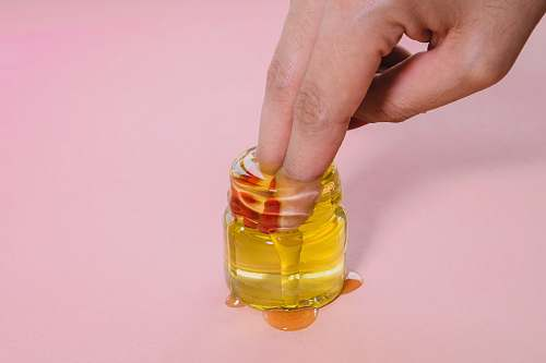 person jar of oil finger