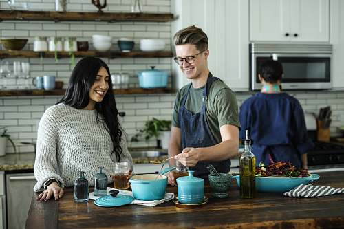 person smiling man standing and mixing near woman in kitchen area of the house kitchenware