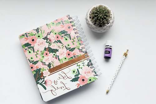 book white and pink floral notebook on table pen