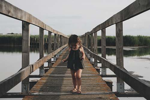 human girl wearing black camisole walking on dock person