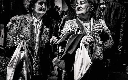 human grayscale photo of two women holding bags person