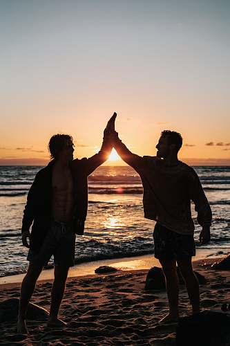 ocean two men clapping each other on shore nature