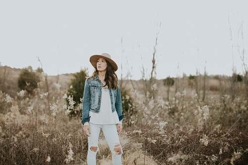 person woman in blue denim jacket surrounded by grass during daytime human