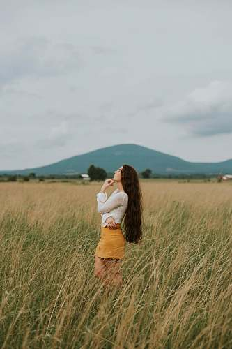 person woman standing in the middle of grass field nature