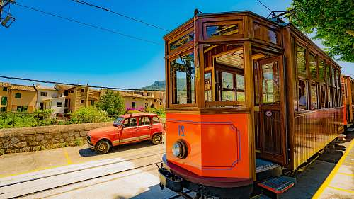 tram red train passing through rails beside red vehicle spain