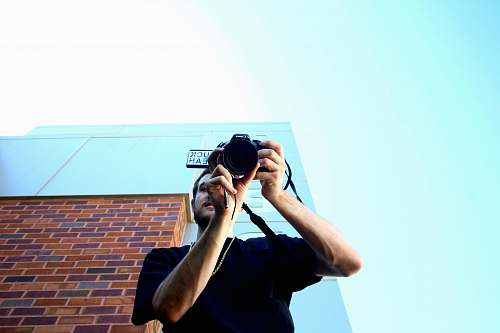 photo person man standing and using DSLR camera human free for commercial use images