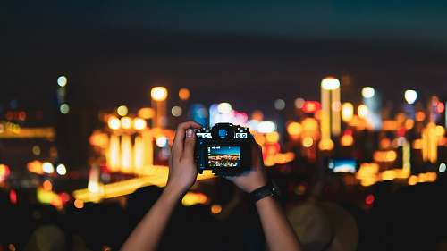 person man taking photo of lighted city skyline at night with DSLR camera human