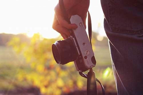 hand person holding bridge camera during daytime sunlight