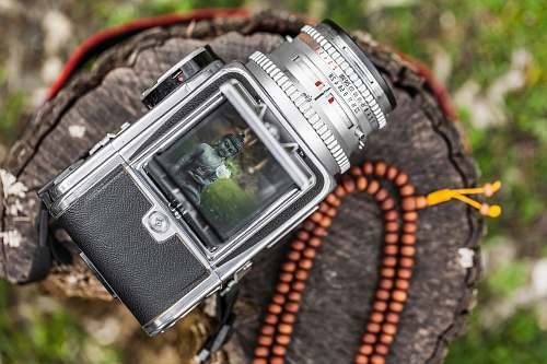 nature selective focus of gray DSLR camera captured Buddha statue digital watch