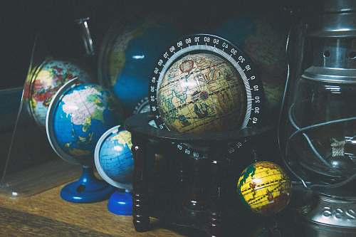 photo sphere assorted mini desk globes on shelf near gray kerosene lantern planet free for commercial use images