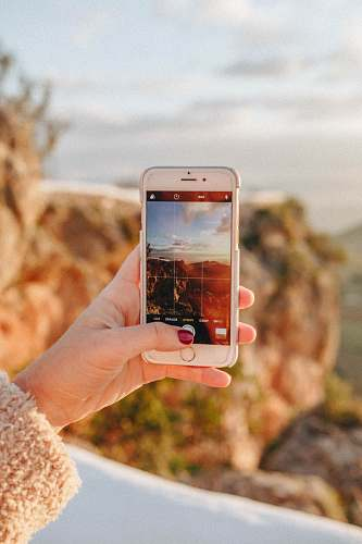 casares person taking a photo of scenery during sunset holding