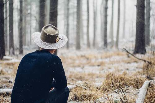 cowboy hat person sitting in grass field forest