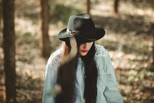 apparel woman wearing blue long-sleeved shirt and black fedora hat clothing