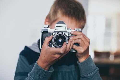 person boy holding gray camera camera