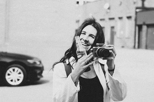 photo person grayscale photography of person smiling holding bottle and camera black-and-white free for commercial use images