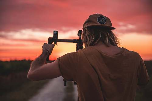 photo person man holding camera with stabilizer during golden hour apparel free for commercial use images