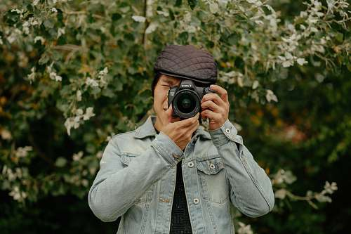 photo person man holding DSLR camera near plants camera free for commercial use images