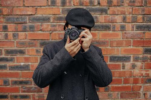 person man holding DSLR camera camera