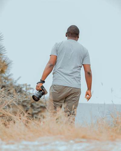 photo person man holding DSLR camera while walking photo free for commercial use images
