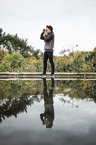photo person man standing near body of water using camera photo free for commercial use images