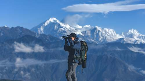 person man standing on top of mountain holding binoculars photo