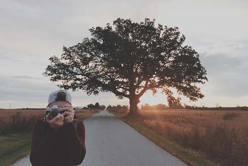 person man taking photos using gray DSLR camera people