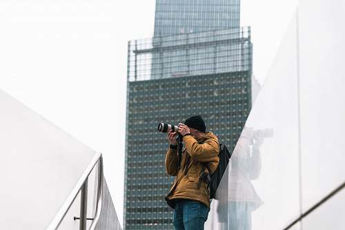 person man taking picture near building a daytime photography