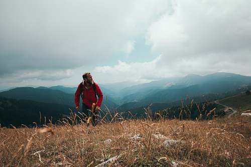 outdoors man wearing red jacket standing on the field nature