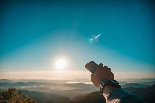 person person holding iPhone overlooking sun and mountains flare