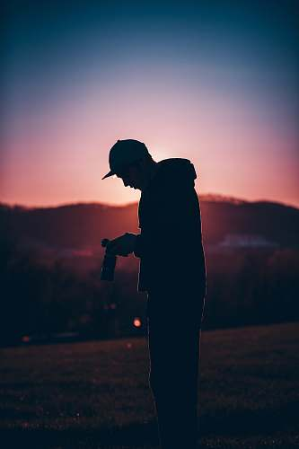 person silhouette of man holding camera silhouette
