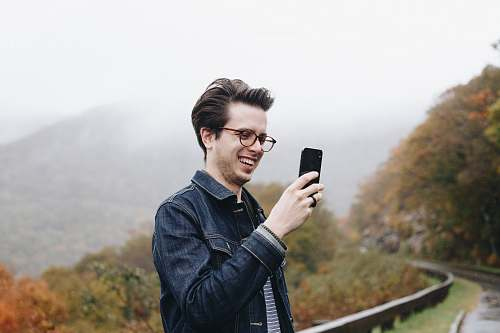 photo person smiling man looking at his smartphone mobile phone free for commercial use images