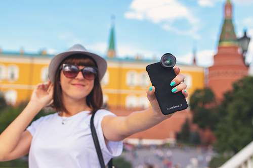 photo person woman holding smartphone with clip lens accessories free for commercial use images