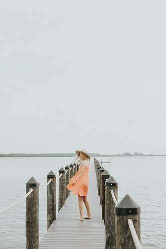 people woman in orange spaghetti strap mini dress standing on brown wooden dock during daytime woman