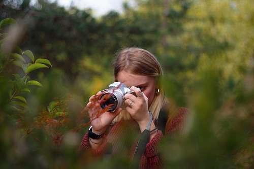 person woman taking photo using DSLR camera camera