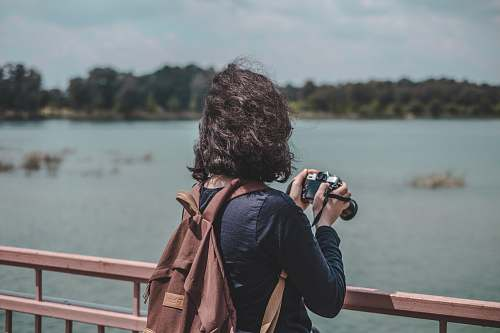 person woman wearing black shirt and brown backpack holding camera standing near railings near body of water photographer